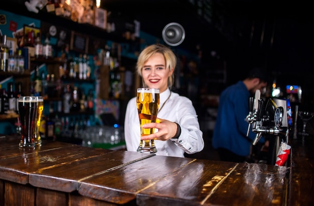 Confident woman tapster makes a show creating a cocktail while standing near the bar counter in pub