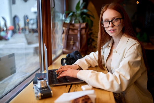 Confident woman traveler using laptop computer in cafe, working at coffee shop.