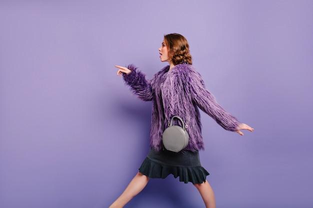 Fiduciosa donna in cappotto di pelliccia alla moda e vestito a piedi passato sfondo viola