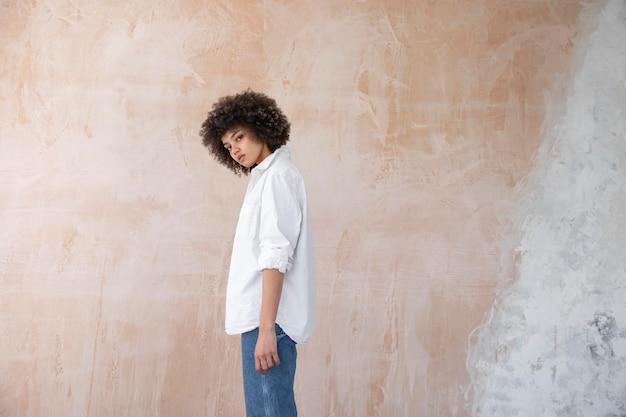 Donna sicura con la posa dei capelli ricci