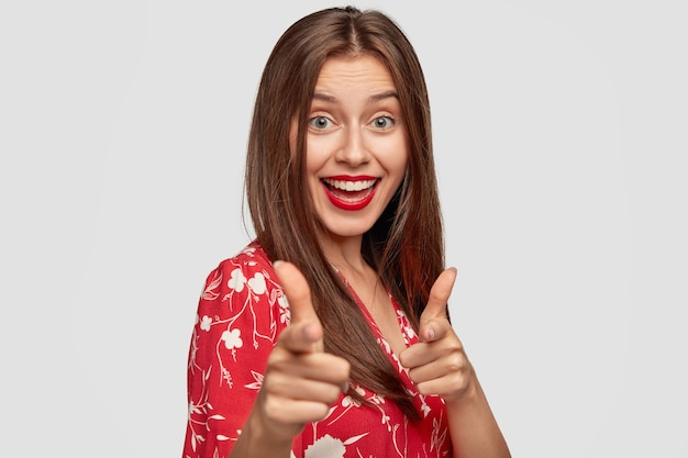 白い壁にポーズをとって赤い口紅で自信を持って女性