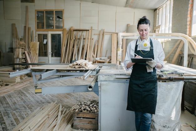 그녀의 자신의 woodshop에서 목수로 일하는 자신감이 여자. 그녀는 태블릿 pc를 사용합니다.