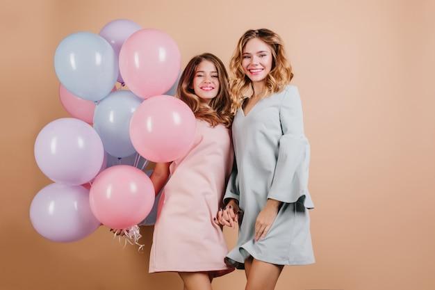 パーティー風船を保持しているピンクのドレスで自信を持って女性