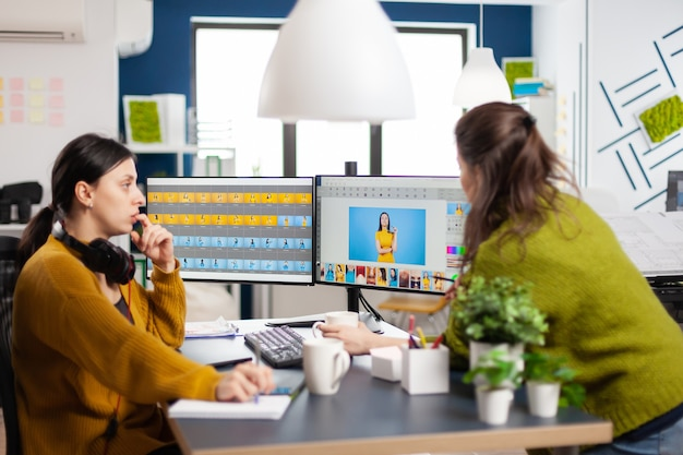 Fiduciose donne editor di foto seduti al posto di lavoro in studio creativo ritocco foto, art director che spiega la tecnica di greding del colore