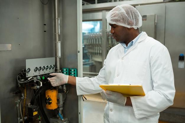 Уверенный работник, работающий с машиной на фабрике соков