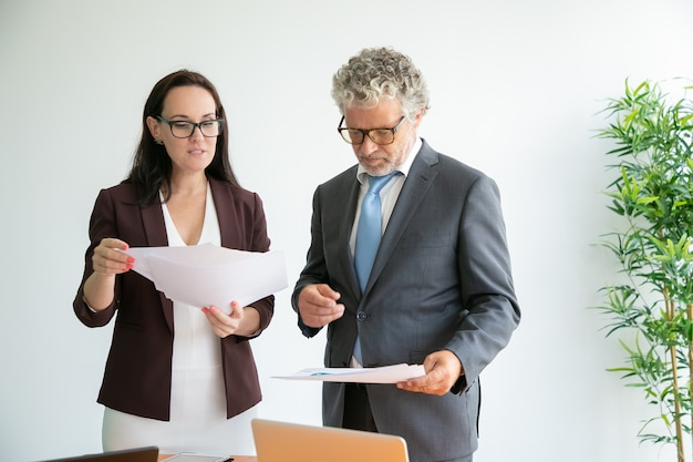 Confident workers in glasses reading documents, talking and standing near table