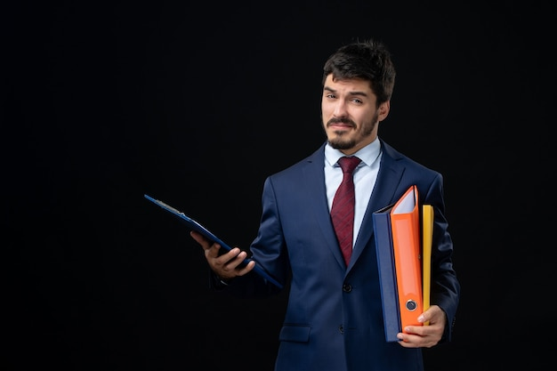 Confident young adult in suit holding several documents on isolated dark wall