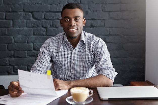 Confident young african businessman wearing formal shirt sitting at table with laptop, mug and papers