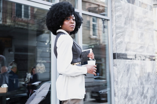 Confident young african businesswoman standing outside the office holding digital tablet and disposable coffee cup
