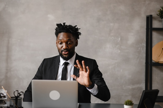Уверенный молодой африканец смотрит на видеоконференцию веб-камеры в офисе