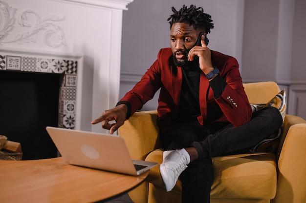 Уверенный молодой африканец смотрит на видеоконференцию веб-камеры