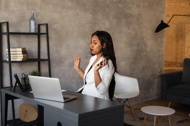 Уверенная молодая африканская женщина смотрит на видеоконференцию по веб-камере в офисе, счастливый предприниматель смешанной расы разговаривает, проводит собеседование в онлайн-видеочате, сидит за столом