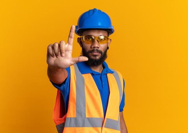 コピースペースのあるオレンジ色の壁に隔離された上向きの安全ヘルメットと制服を着た安全メガネの自信を持って若いアフリカ系アメリカ人ビルダーの男