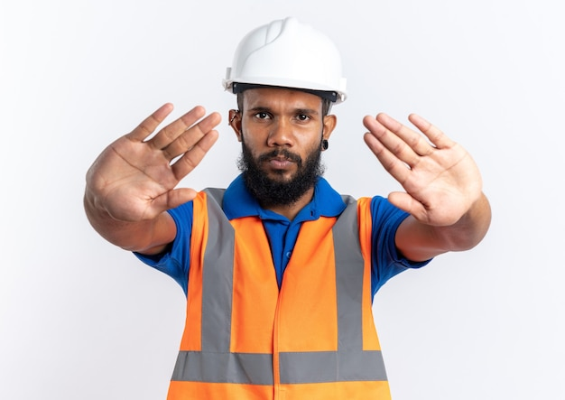 Уверенный молодой афро-американский строитель человек в форме с защитным шлемом, жестикулирующий знак остановки, изолированный на белом фоне с копией пространства