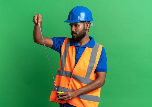 안전 헬멧을 들고와 복사 공간이 녹색 배경에 고립 된 테이프 측정을보고 제복을 입은 자신감이 젊은 아프리카 계 미국인 작성기 남자