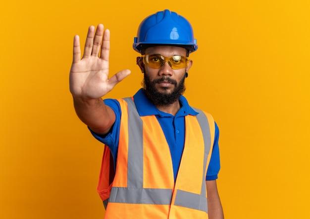 Fiducioso giovane costruttore afro-americano uomo in occhiali di sicurezza che indossa l'uniforme con casco di sicurezza che gesturing il segnale di stop isolato sulla parete arancione con spazio di copia