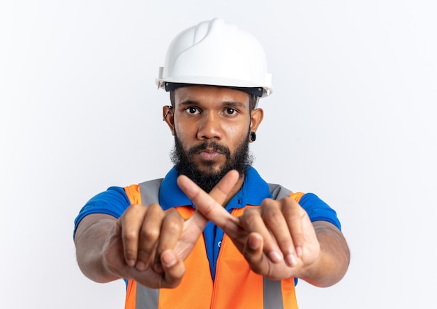 Confident young afro-american builder man in uniform with safety helmet crossing his fingers gesturing no sign isolated on white background with copy space