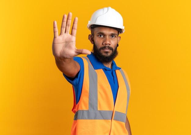 Fiducioso giovane costruttore afro-americano in uniforme con casco di sicurezza che fa gesto di arresto isolato su sfondo arancione con spazio di copia