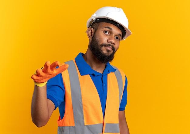 Fiducioso giovane costruttore afroamericano uomo in uniforme con casco di sicurezza e guanti che tiene la mano aperta isolata su sfondo arancione con spazio di copia