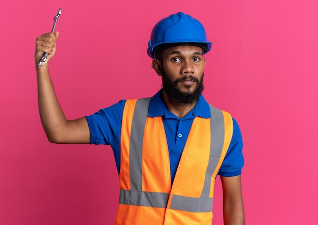 Confident young afro-american builder man in uniform with safety helmet holding workshop key isolated on pink background with copy space