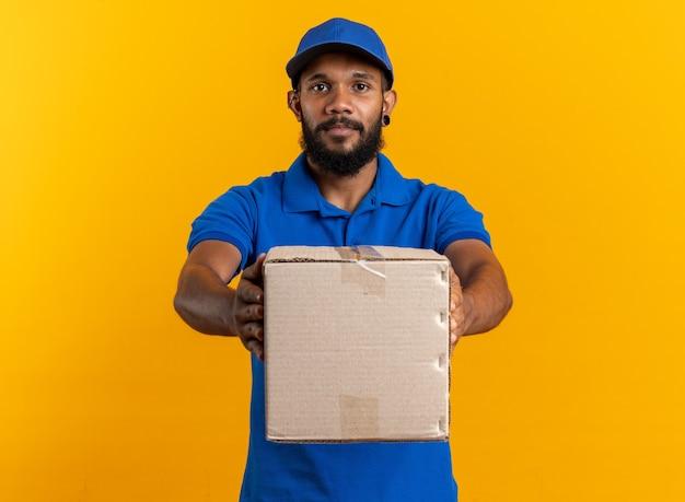 Уверенный молодой афро-американский курьер, держащий картонную коробку, изолированную на оранжевом фоне с копией пространства