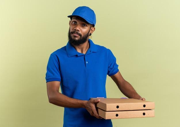 Уверенный молодой афро-американский курьер, держащий коробки для пиццы, изолированные на оливково-зеленой стене с копией пространства