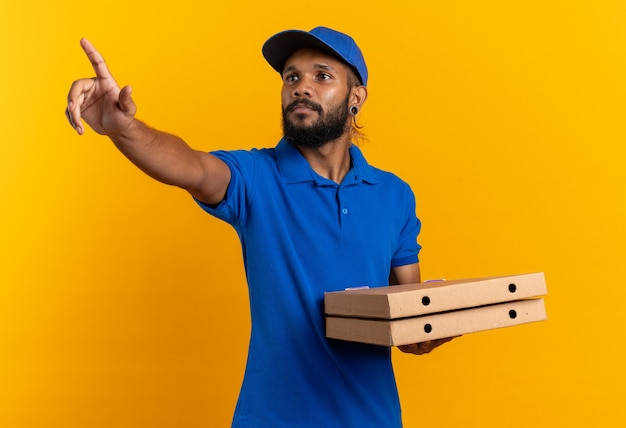 Confident young afro-american delivery man holding pizza boxes and pointing at side isolated on orange background with copy space