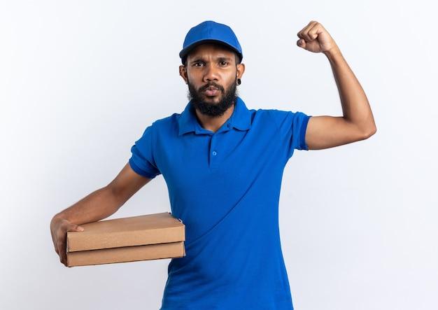 Fiducioso giovane afro-americano fattorino che tiene scatole per pizza e alza il pugno isolato su sfondo bianco con spazio di copia copy