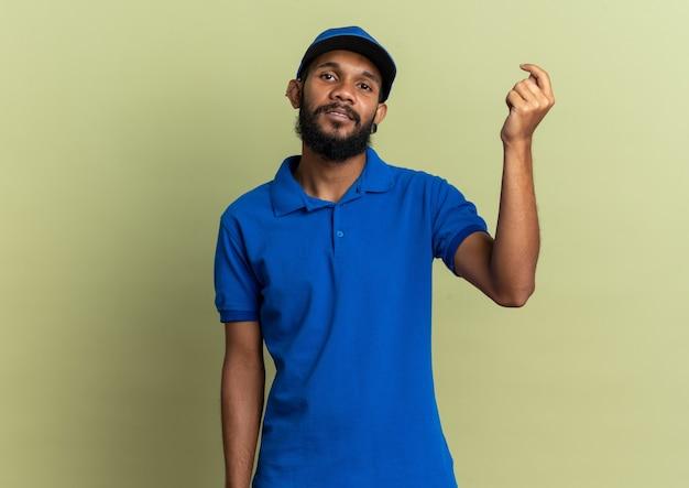 Fiducioso giovane fattorino afroamericano che finge di tenere qualcosa di isolato su sfondo verde oliva con spazio di copia