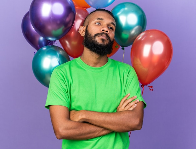 Confident young afro-american guy wearing green t-shirt standing in front balloons crossing hands isolated on blue wall