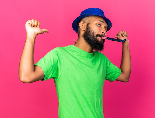 Confident young afro-american guy wearing party hat blowing party whistle points at himself