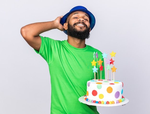Confident  young afro-american guy wearing party hat holding cake isolated on white wall