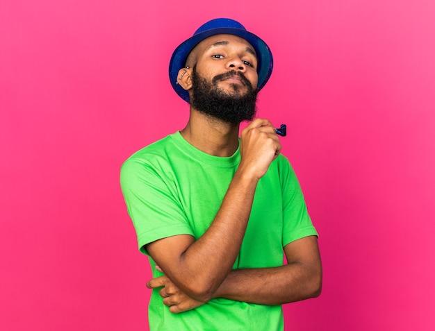 ピンクの壁に分離されたパーティーホイッスルを保持しているパーティーハットを身に着けている自信を持って若いアフリカ系アメリカ人の男