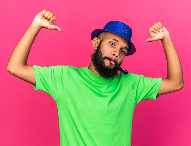 Confident young afro-american guy wearing party hat points at himself