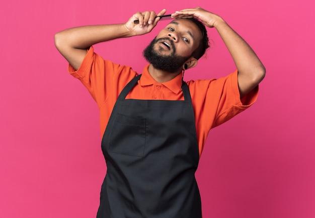 Fiducioso giovane barbiere maschio afro-americano che indossa l'uniforme che si pettina i capelli isolati sulla parete rosa