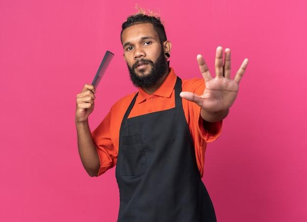 Уверенный молодой афро-американский мужчина-парикмахер в униформе держит гребень и делает стоп-жест
