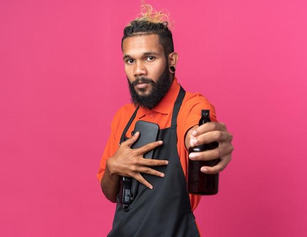 自信を持って若いアフリカ系アメリカ人の男性の理髪師は、正面に向かってヘアスプレーを伸ばして正面を見て理髪店のツールを保持している縦断ビューで制服を着ています