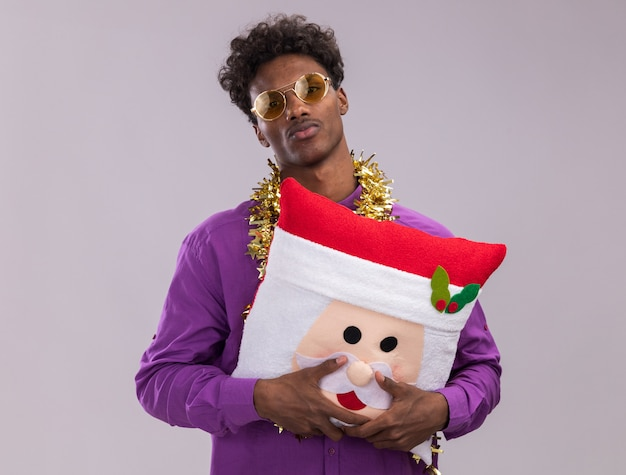 Confident young afro-american man wearing glasses with tinsel garland around neck holding santa claus pillow looking at camera isolated on white background