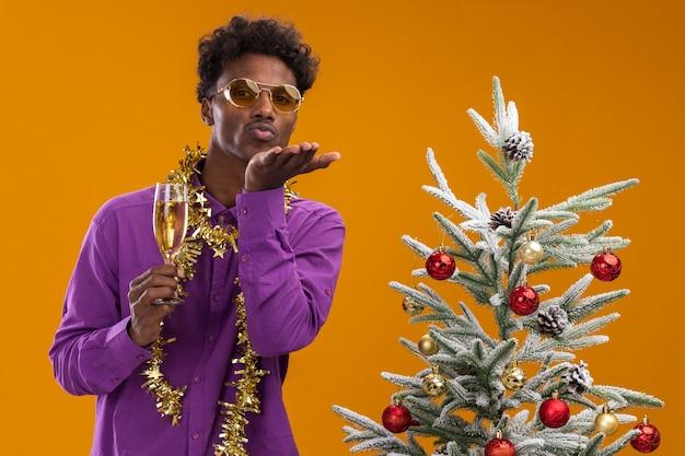 シャンパンのガラスを保持している装飾されたクリスマスツリーの近くに立っている首の周りに見掛け倒しの花輪と眼鏡をかけている自信を持って若いアフリカ系アメリカ人の男