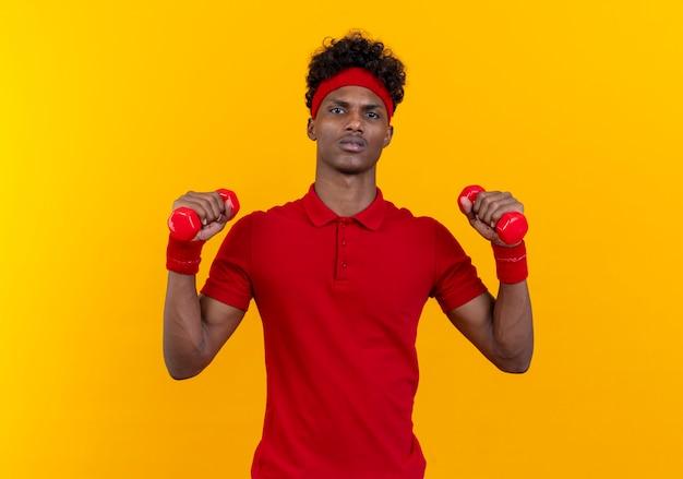 노란색 벽에 고립 된 아령으로 운동 머리띠와 팔찌를 착용 자신감 젊은 아프리카 계 미국인 스포티 한 남자