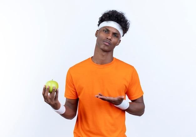 自信を持って若いアフリカ系アメリカ人のスポーティな男は、ヘッドバンドとリストバンドを持って、リンゴを手で指しています