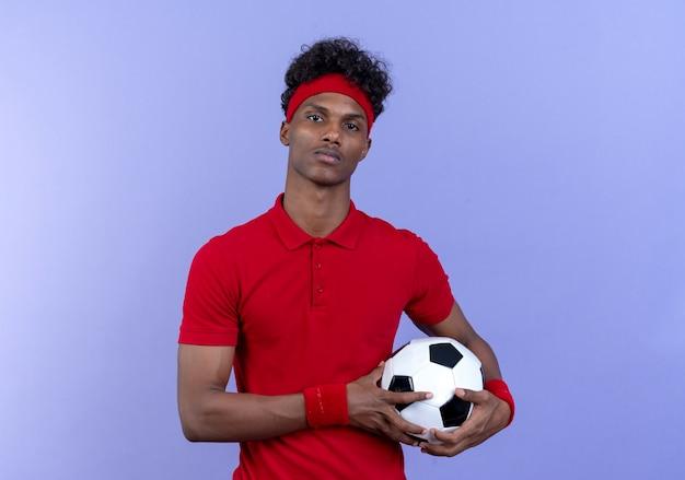 파란색 벽에 고립 된 머리띠와 팔찌를 들고 공을 들고 자신감 젊은 아프리카 계 미국인 스포티 한 남자