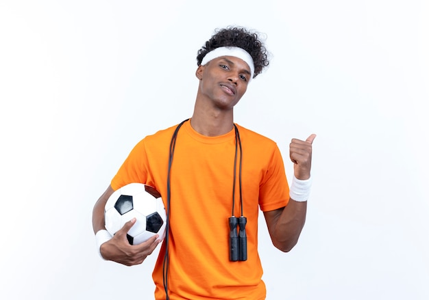 自信を持って若いアフリカ系アメリカ人のスポーティな男は、肩に縄跳びとコピースペースで白い背景で隔離の側のポイントでボールを保持しているヘッドバンドとリストバンドを身に着けています