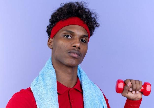 青い壁に分離された肩にタオルでダンベルを保持しているヘッドバンドとリストバンドを身に着けている自信を持って若いアフリカ系アメリカ人のスポーティな男