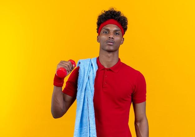 黄色の壁で隔離の肩にタオルでダンベルを保持しているヘッドバンドとリストバンドを身に着けている自信を持って若いアフリカ系アメリカ人のスポーティな男