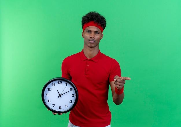 壁時計を保持し、緑の背景に分離されたジェスチャーを示すヘッドバンドとリストバンドを身に着けている自信を持って若いアフリカ系アメリカ人のスポーティな男