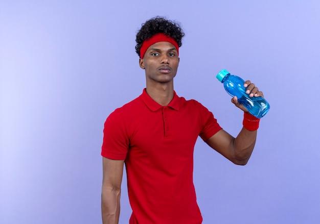 Fiducioso giovane uomo sportivo afro-americano che indossa la fascia e il braccialetto che tiene la bottiglia di acqua isolata sulla parete blu