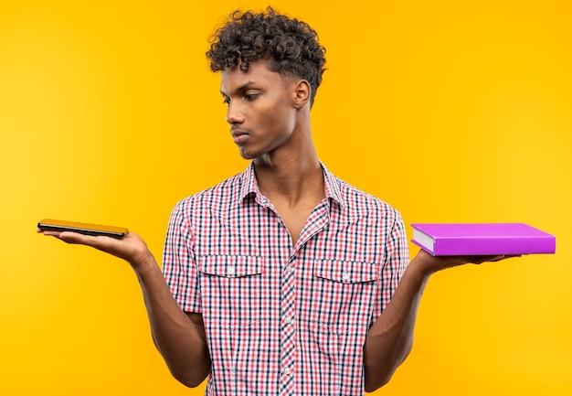 電話と本を持っている自信を持って若いアフリカ系アメリカ人の学生