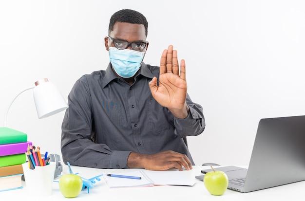 Fiducioso giovane studente afroamericano in occhiali ottici che indossa una maschera medica seduto alla scrivania con strumenti scolastici che gesturing il segnale di stop isolato sul muro bianco
