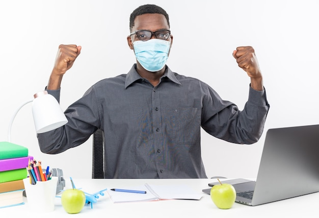 Fiducioso giovane studente afroamericano in occhiali ottici che indossa una maschera medica seduto alla scrivania con strumenti scolastici che tengono i pugni isolati sul muro bianco